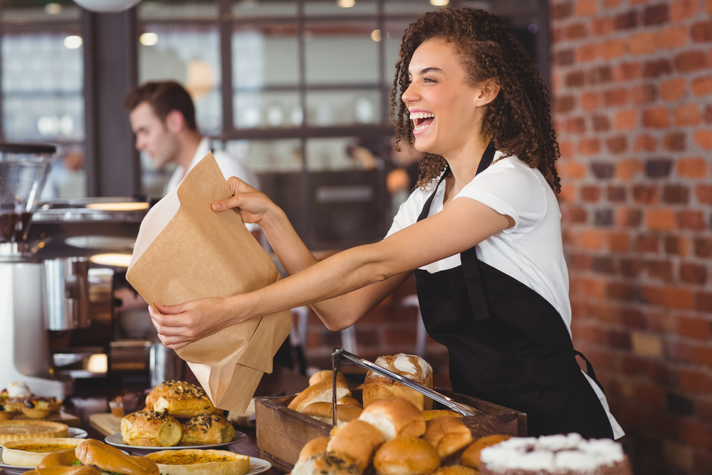 Smiling waitress bagging food to go