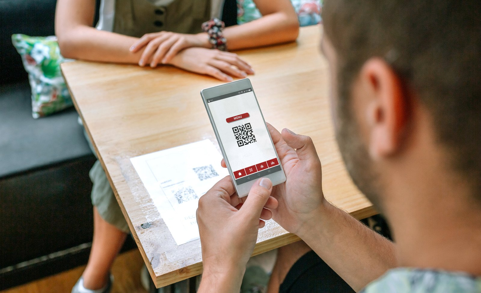 Customer in a restaurant ordering with a QR code scan