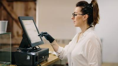 Woman typing something into POS terminal