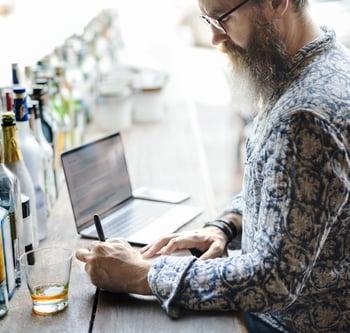 Man behind bar taking inventory
